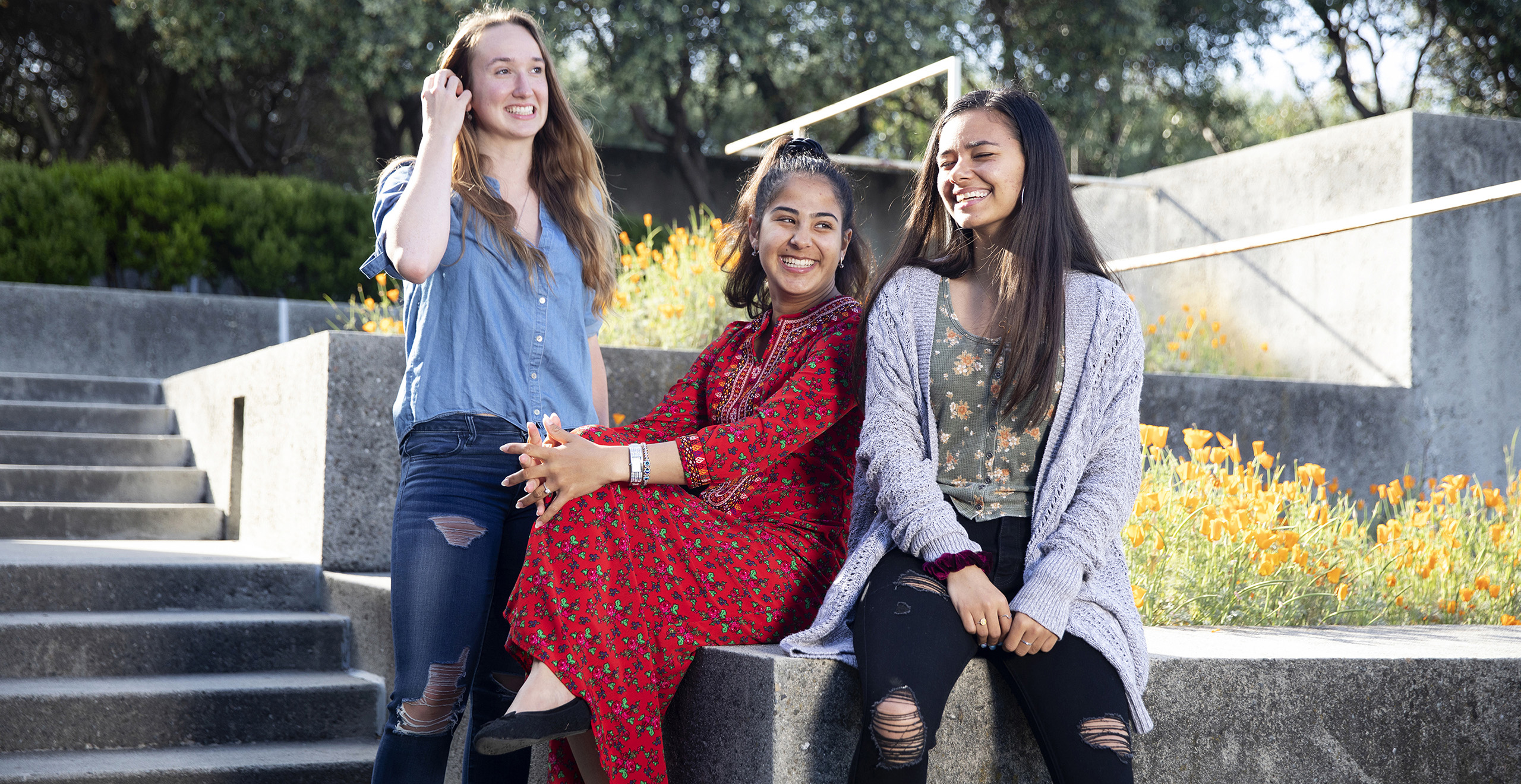 Three Holy Names University students talking on campus steps