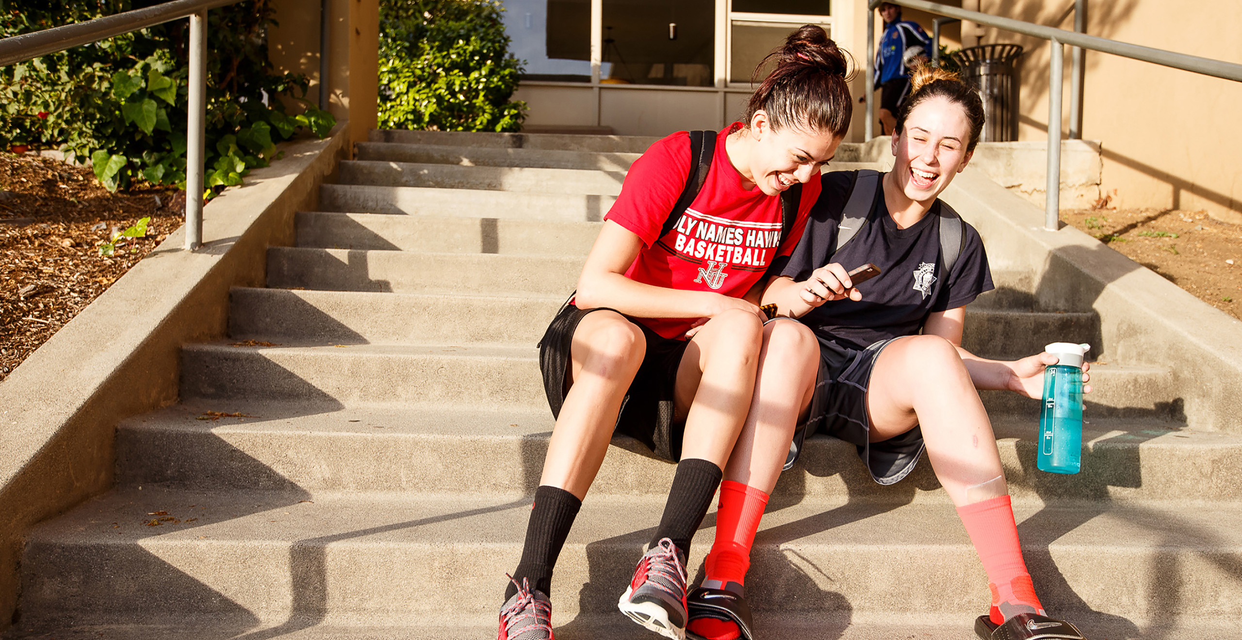 Two Holy Name University students sitting on campus steps