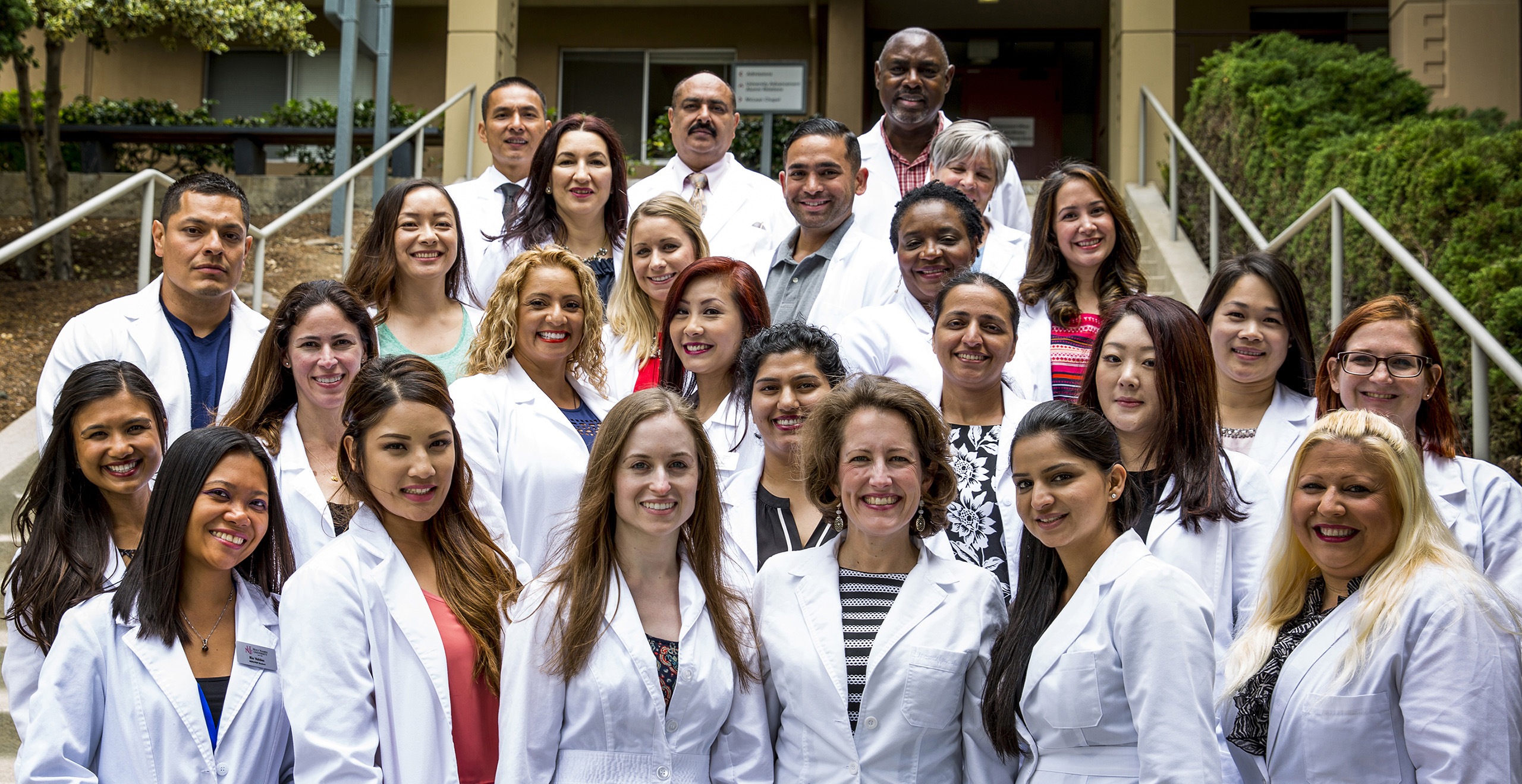 Holy Name University MSN students in their white coats on campus steps