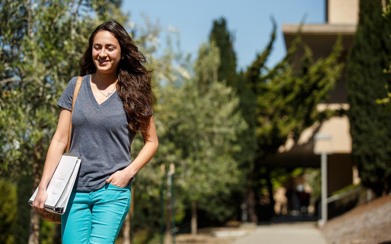 student walking down Holy Name University steps