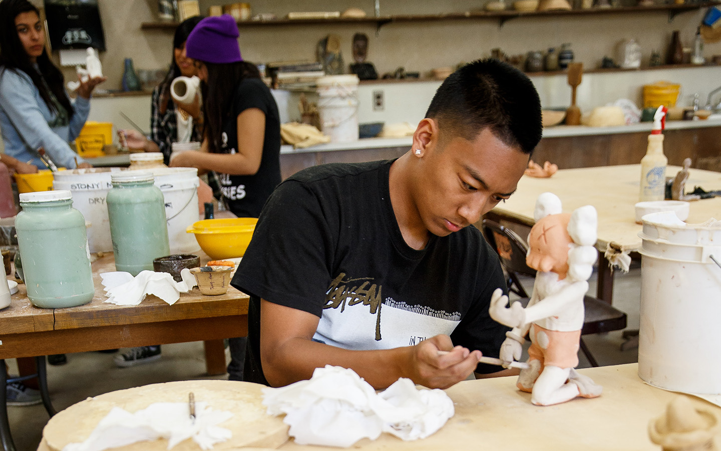 HNU student working on their pottery art project