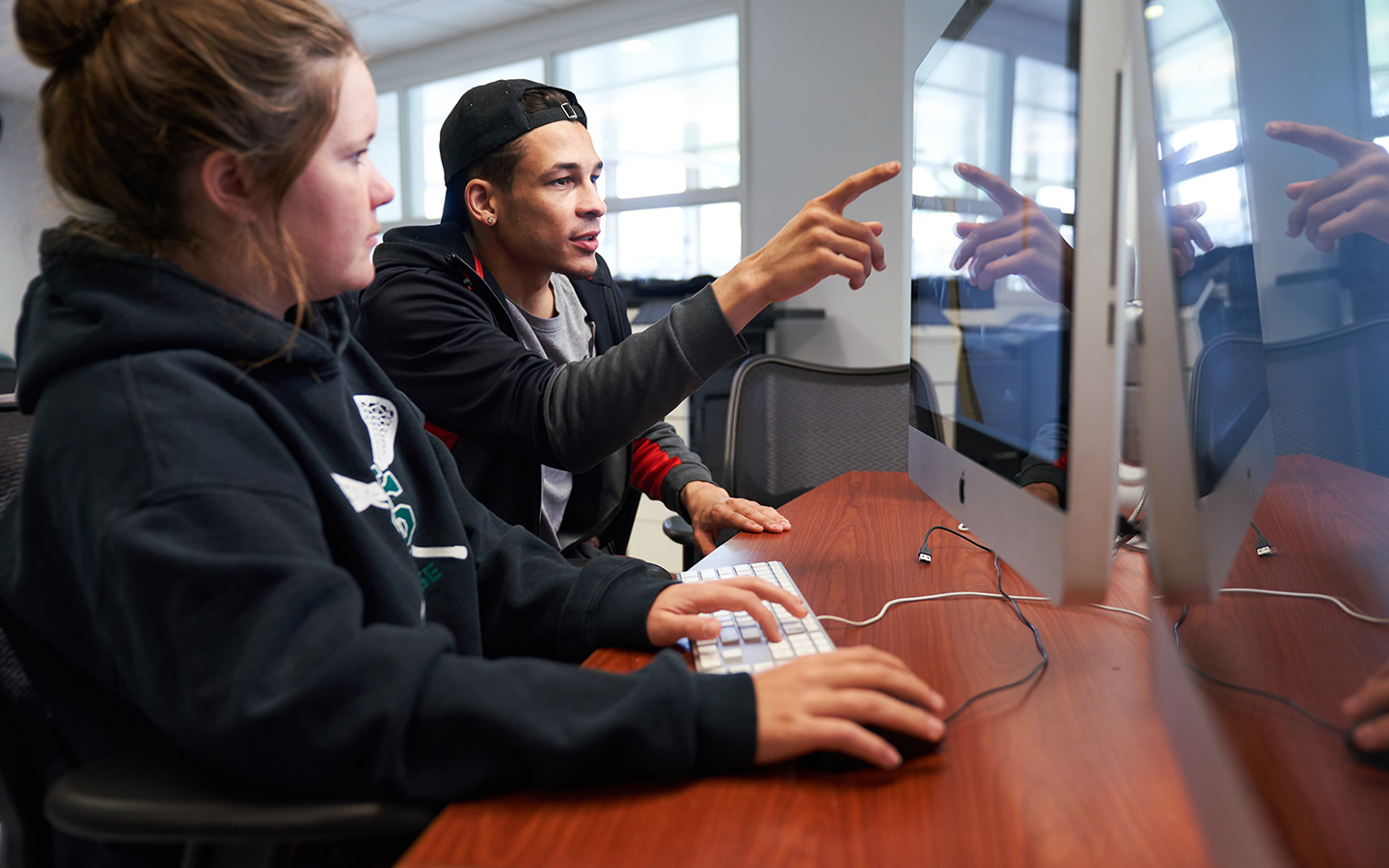 Two HNU students working on a computer together