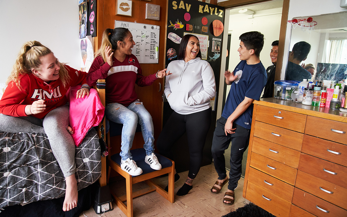 Holy Names University students laughing in dorm room