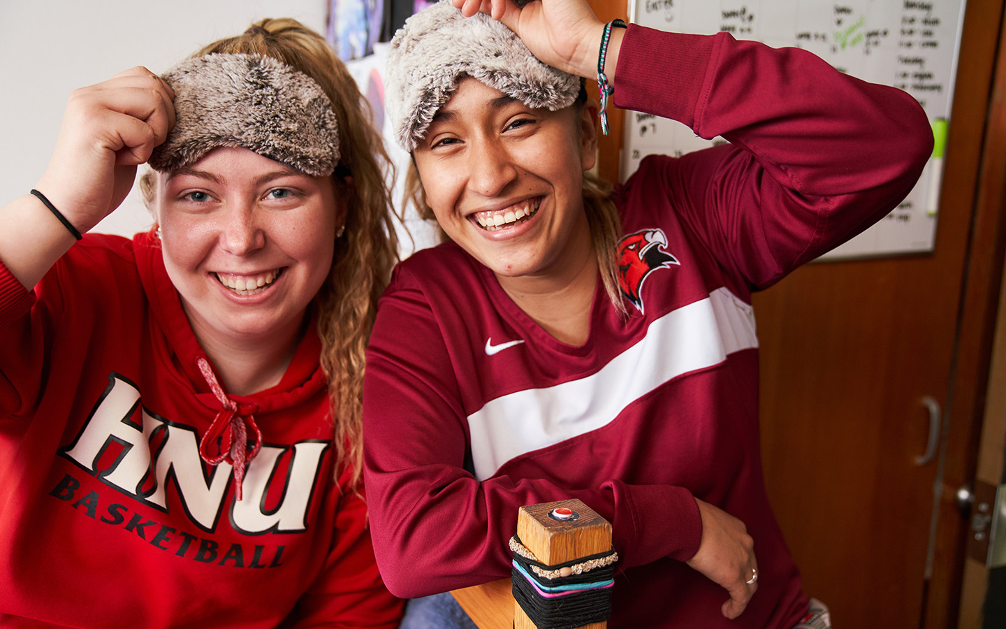 Two Holy Name University students in dorm room with sleep masks on