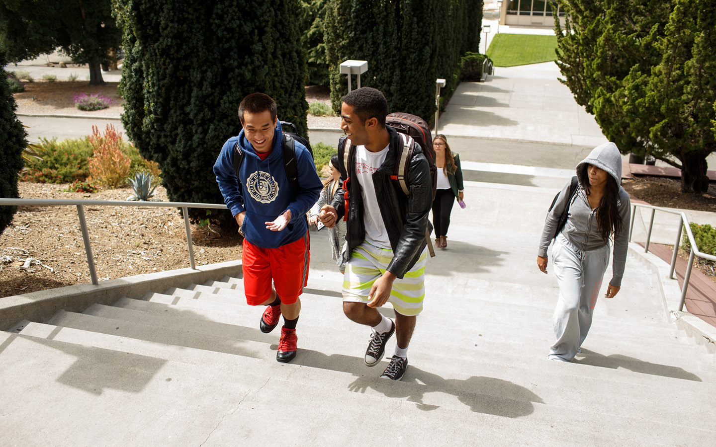 two Holy Names University students talking and walking up campus steps