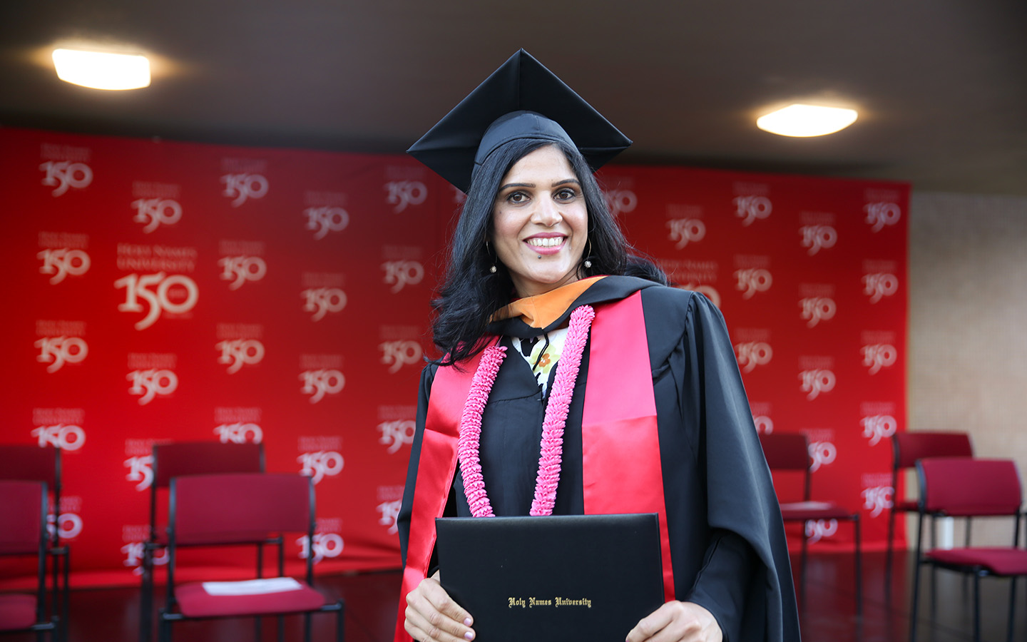 HNU Student posing with their degree at commencement ceremony