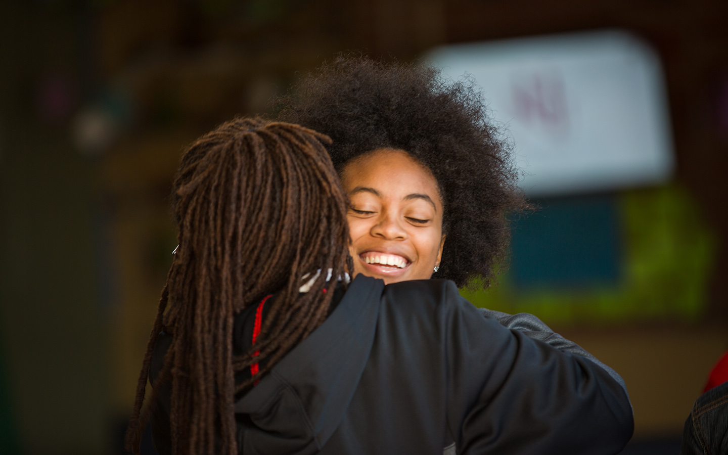 Two HNU students hugging after graduation ceremony