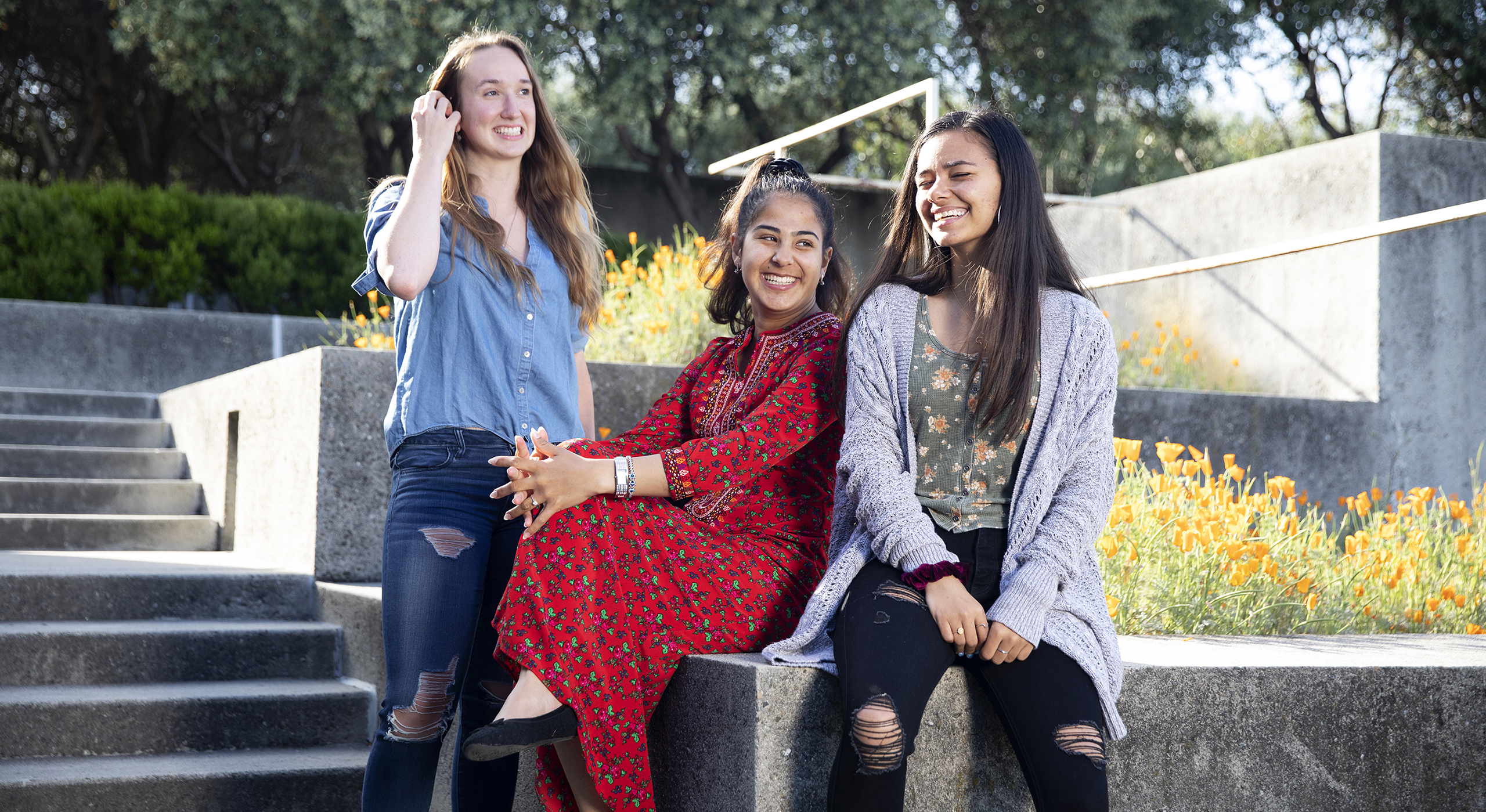 three Holy Names University students sitting on campus stairs