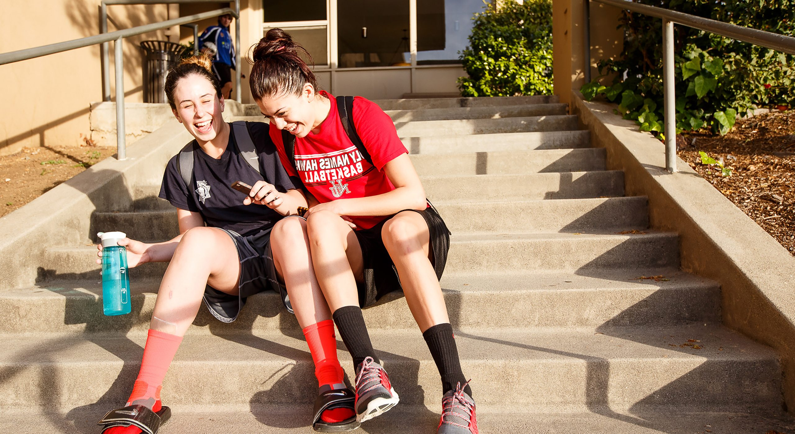 two Holy Names University athletes sitting on stairs