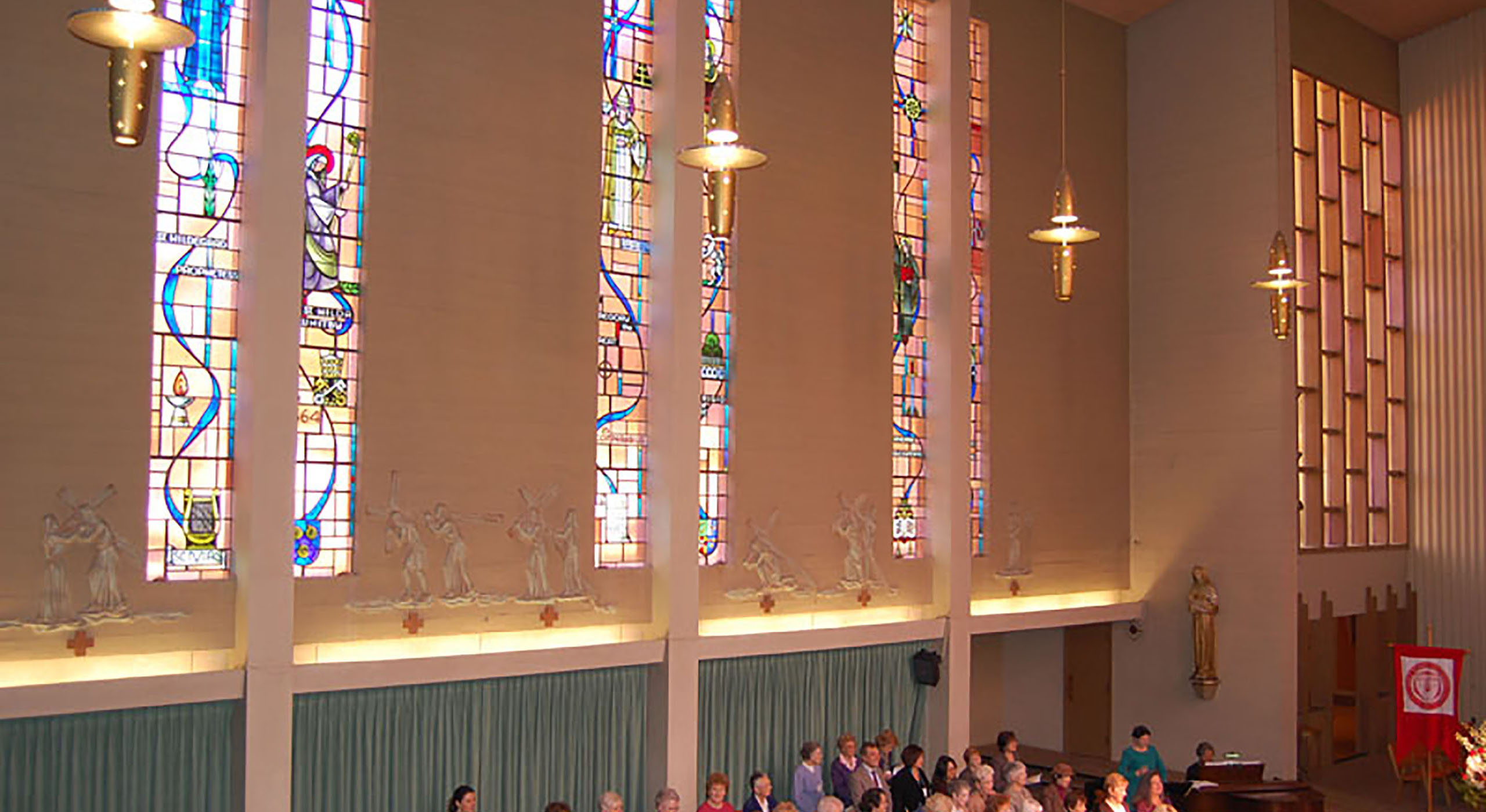 stained glass windows in church with attendants standing below