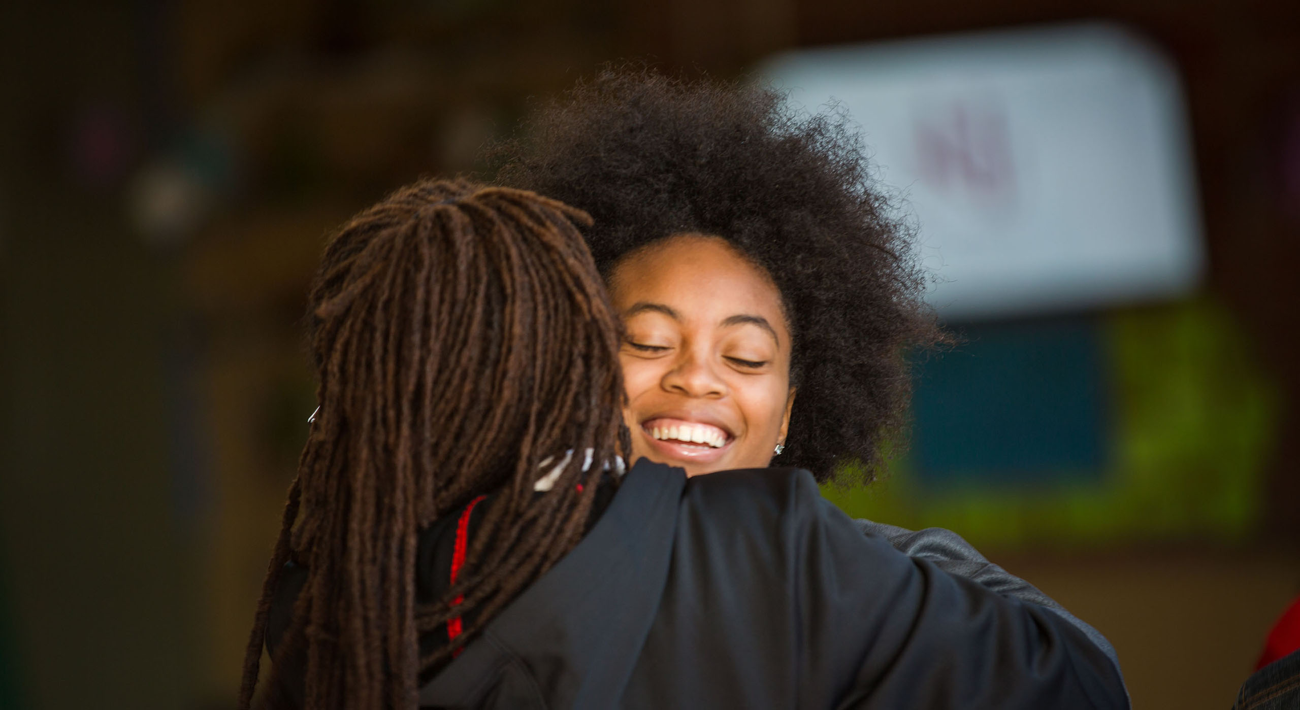 Two Holy Names University students hugging on graduation day
