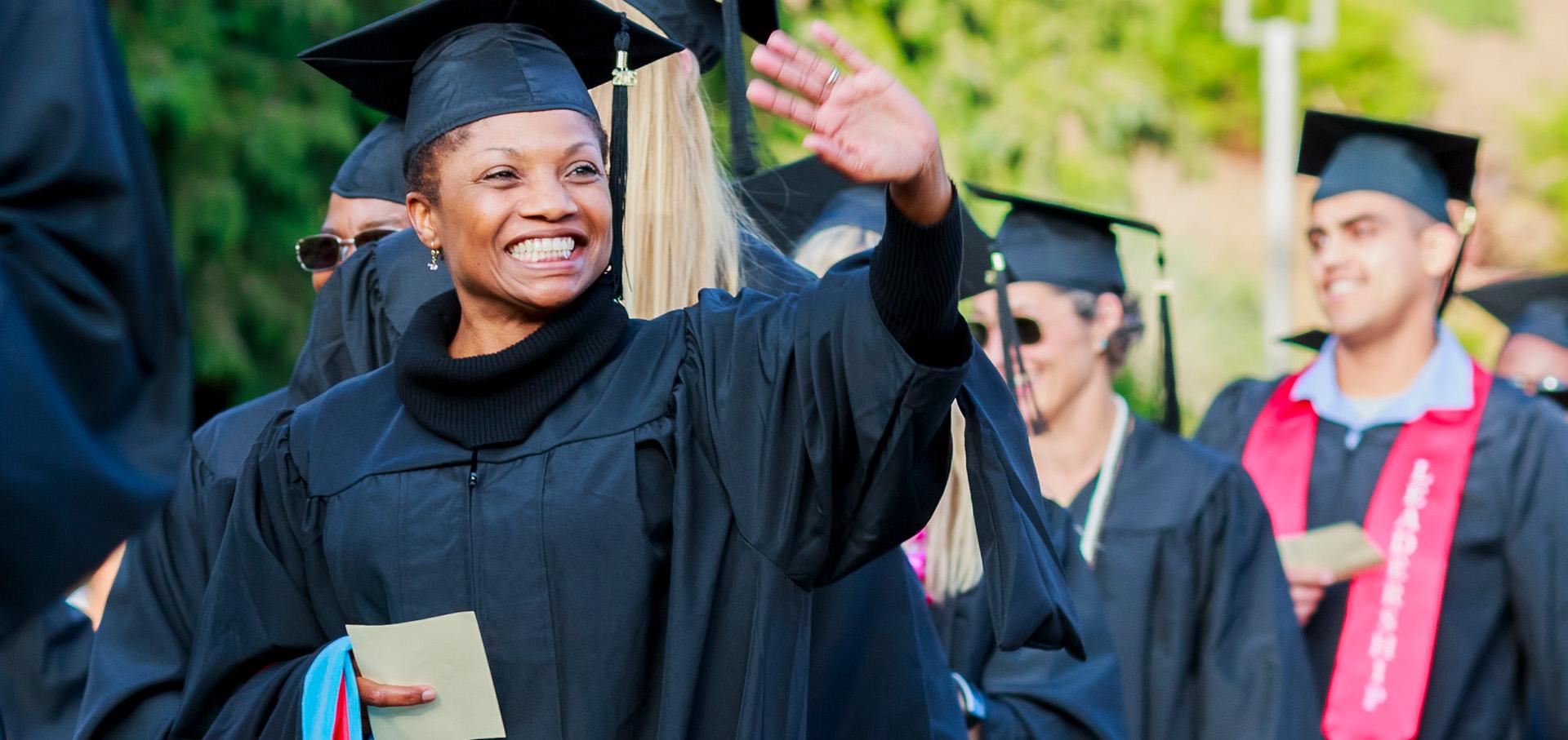 A waving HNU graduate