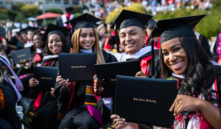 Holy Names University graduates showing off diplomas at graduation