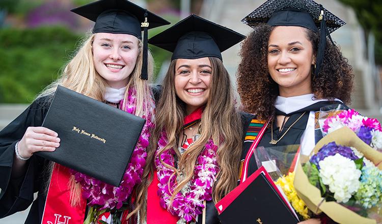 three HNU graduates posing together after graduation ceremony