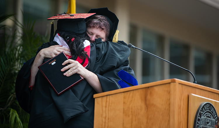 HNU faculty hugs a graduate during commencement ceremony