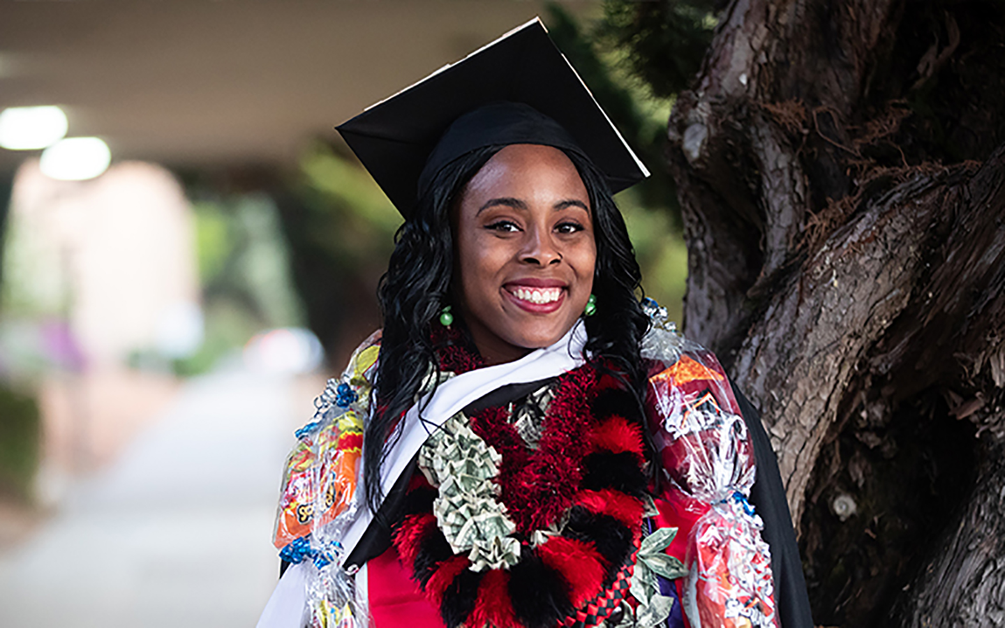 Holy Names University 2019 graduate smiling in cap and gown