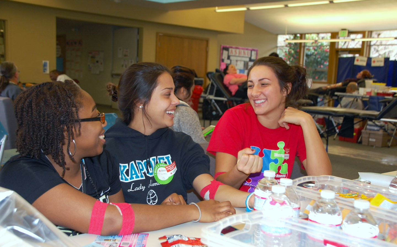 three Holy Names University students at a blood drive
