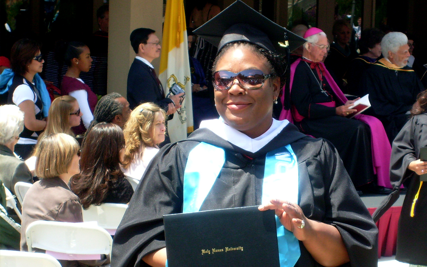 Letteria Fletcher in cap and gown on graduation day holding degree