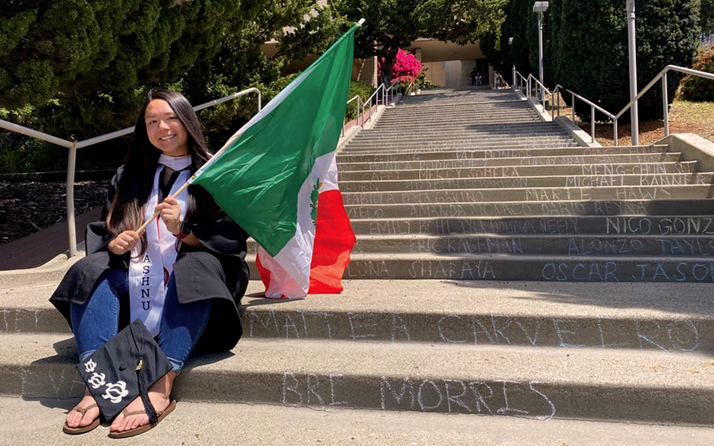 Holy Names University student Mattea Carveiro in cap and gown holding flag of Mexico