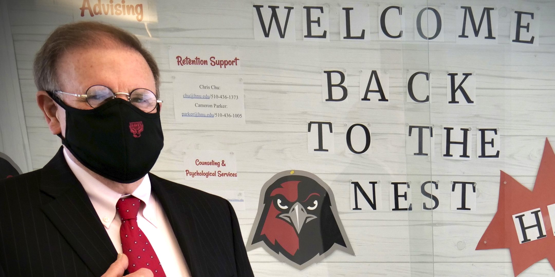 HNU President Mike Groener in front of welcome back bulletin board