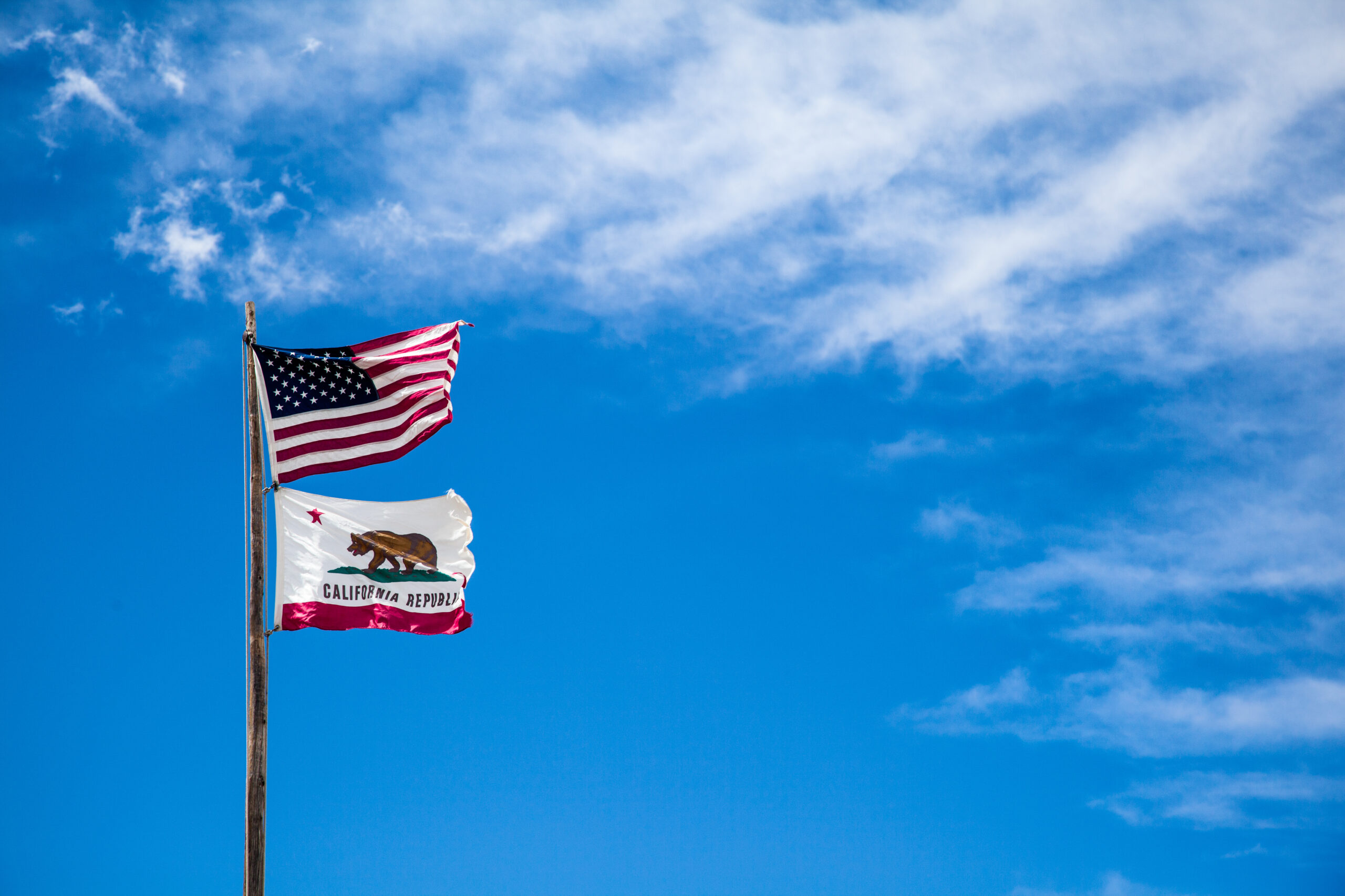 American flag and California Republic flag waving in blue sky